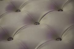Buttoned white leather wall. With vignetting on padding background Stock Photo