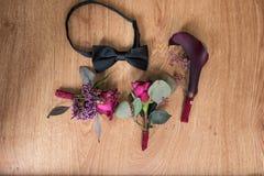 Buttonhole τριών διακοσμήσεων και μια μαύρη γραβάτα στο καφετί υπόβαθρο Διακόσμηση φιαγμένη από τριαντάφυλλα, διακοσμητικές εγκατ στοκ φωτογραφία με δικαίωμα ελεύθερης χρήσης
