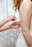 Buttoning bride's wedding dress. Close up. stock photos