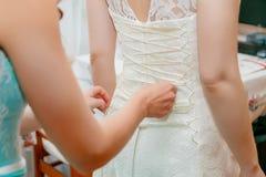 Buttoning bride's wedding dress. Close up. royalty free stock photos