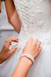 Buttoning bride's wedding dress. Close up. Stock Photography
