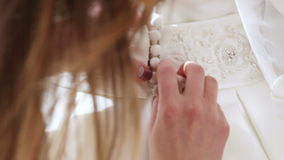 Buttoning buttons on wedding dress stock footage