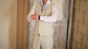 Buttoning cuffs. The groom wears cufflinks. Businessman inserts stock video footage
