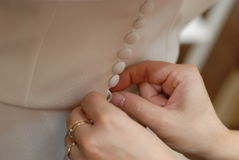 Buttoning a dress. A closeup of a pair of hands, helping to button up a bride's dress Stock Photos