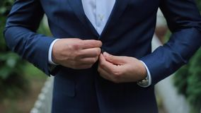 Buttoning a Jacket. Stylish Man in a Suit Fastening Buttons on His Jacket Preparing to Go Out Close up stock video