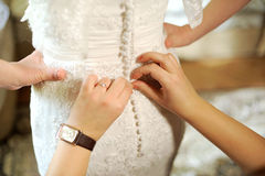 Buttoning Wedding Dress Stock Image