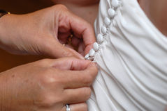 Buttoning Wedding Dress. Closeup of a woman buttoning a row of buttons on a bridal dress Royalty Free Stock Images