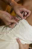 Buttoning into Wedding Dress. A bride has her dress buttoned in preparation for the wedding Royalty Free Stock Image