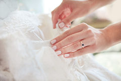 Buttoning wedding dress Stock Image