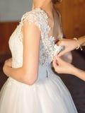 Buttoning Wedding Dress Stock Photo