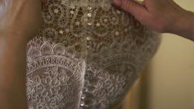 Buttoning wedding dress stock footage