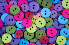 Buttons. A pile of multi colored clothing buttons fill the frame Stock Image
