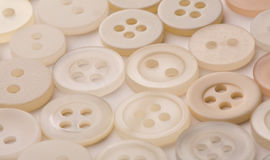 Buttons. White sew-through buttons laid out in soft light royalty free stock photos