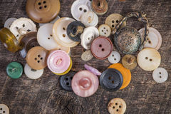 Buttons on barn wood. Buttons scattered on old dark barn wood Stock Photo