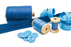Buttons, blue zipper and spools of thread Stock Photography