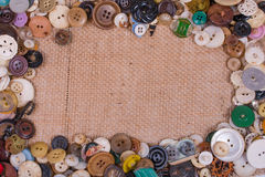 Buttons bordering burlap. Old buttons around the borders of burlap fabric Stock Image