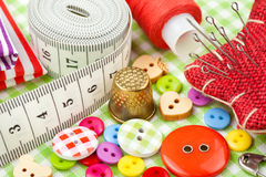 Buttons, colorful fabrics, measuring tape, pin cushion, thimble, spool of thread Stock Images