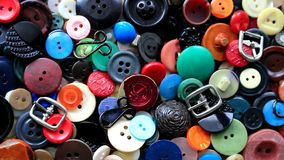 Buttons of different colors. Long ago they decorated costumes and dresses. Buttons of different colors, from big to small, buckles and hooks, they got worn out stock footage