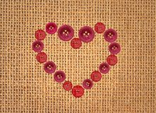 Buttons in heart symbol on linen texture Stock Images