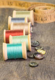 Buttons and measuring tape with thread. Buttons and measuring tape with spools of thread Royalty Free Stock Image