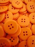 buttons orangen Arkivfoto