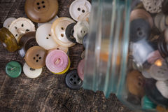 Buttons pouring out of jar. Buttons being poured out of an old blue jar onto old barn wood Royalty Free Stock Images
