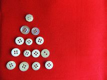 Buttons on red fabric background. Christmas tree. Stock Image