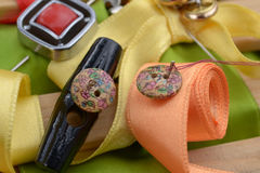 Buttons and ribbons. Black oblong and small button with a needle, orange rolled ribon with small button with needle and thread; red button and pin with two gold royalty free stock photography
