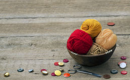 Buttons, scissors and yarn. On a wooden table Stock Image