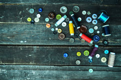 Buttons and sewing spools on planks Stock Image
