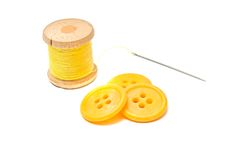Buttons and spool of yellow thread Stock Images