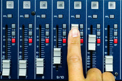 Buttons and tabs in the audio controller. Hand pushing open a fader on a sound desk Stock Photo