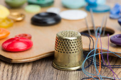 Buttons, thimble, needle and thread on the palette Royalty Free Stock Image