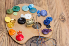 Buttons, thimble, needle and thread on the palette Royalty Free Stock Photo