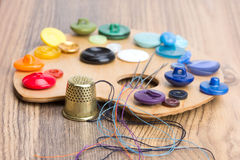 Buttons, thimble, needle and thread on the palette Stock Photo