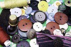 Buttons, threads and thimble are on the table stock image