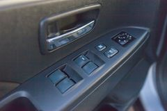 Buttons of window regulators in an automobile door stock photography