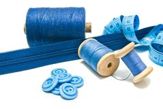Buttons, zipper and spools of blue thread Stock Images