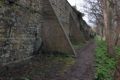 Buttresses. Buttressed stone wall with footpath and trees Royalty Free Stock Photography
