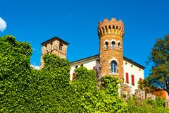 Buttrio castle brick tower. Seen from outide the perimeter crenellated wall covered in ivy, Udine, Friuli, Italy stock photo