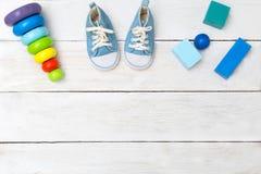 Buty dla chłopiec i drewnianych sześcianów na drewnianym tle Zdjęcia Stock