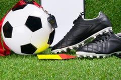 Buty, futbolowa piłka, writing ochraniacz, gwizd i kar karty dla sędziego przeciw tłu trawa, Obrazy Stock