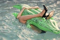 Buty od krokodyl skóry kobieta na morzu z nadmuchiwaną materac Żeńska noga chwyta materac w pływackim basenie Moda obraz stock
