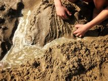 Buulding a sand castle or a dam at the beach in summer Royalty Free Stock Photos