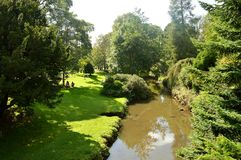 Buxton Pavilion Gardens. Tourists relaxing by the river in Buxton Pavilion Gardens in Derbyshire Royalty Free Stock Image