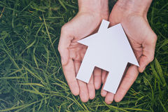 Buy or Build a New Home. Buy or build a new house - two hands of a woman holding a white cutout house over green grass, viewed from the top Royalty Free Stock Photos