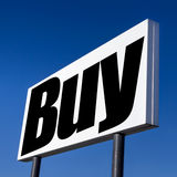 Buy, buy and buy. Horizontal billboard with the order to BUY, against irreal blue sky. Abstract concept of consumerism, human mind control, power of corporations royalty free stock photography