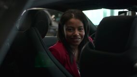 Buy car, portrait of black woman sitting on seat in dealership and smile. Successful happy