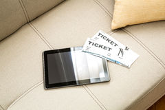 Buy Cinema Tickets online with a Tablet PC. Buy cinema Tickets online with your mobile device or Tablet PC on the sofa stock photo