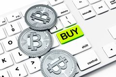 Buy, cryptocurrency and purchase concept. Close up of white keyboard with green button and silver bitcoins. Buy, cryptocurrency and purchase concept. 3D Royalty Free Stock Image